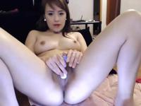 A cute Asian brunette is getting herself off