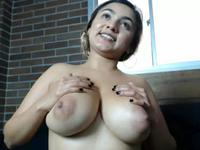 Busty woman is playing with a dildo