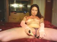 A busty lady is sucking a dildo